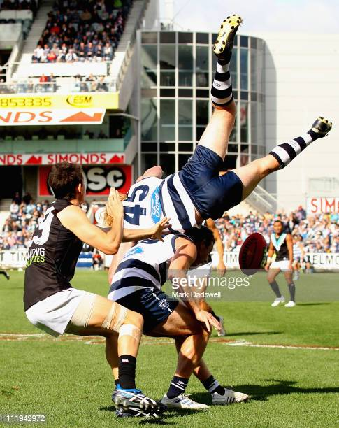 Cameron Ling of the Cats crashes back to the ground after flying for a mark over Steve Johnson during the round three AFL match between the Geelong...