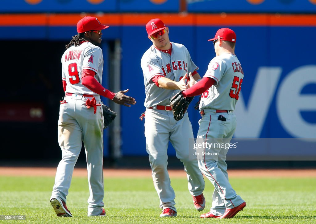 Cameron Maybin #9, Mike Trout #27 and Kole Calhoun #56 of the Los Angeles Angels of Anaheim celebrate after defeating the New York Mets at Citi Field on May 21, 2017 in the Flushing neighborhood of the Queens borough of New York City.