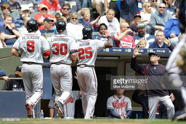 Cameron Maybin of the Atlanta Braves celebrates outside the dugout with Jace Peterson and Ryan Lavarnway a three run homer in the third inning...