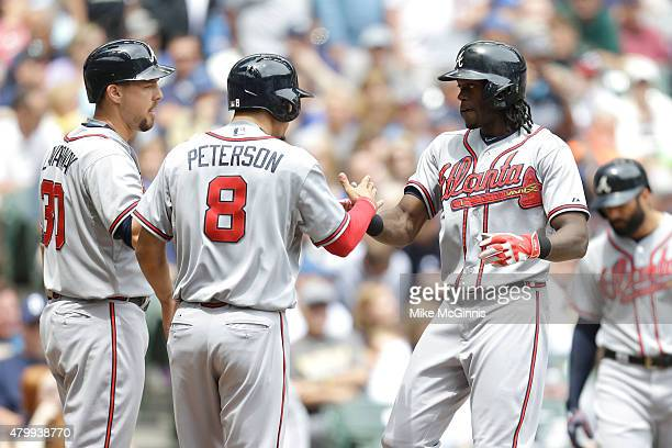 Cameron Maybin of the Atlanta Braves celebrates with Jace Peterson and Ryan Lavarnway a three run homer in the third inning against the Milwaukee...