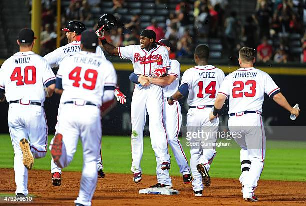 Cameron Maybin of the Atlanta Braves is congratulated by teammates after knocking in the gamewinning run against the Washington Nationals at Turner...