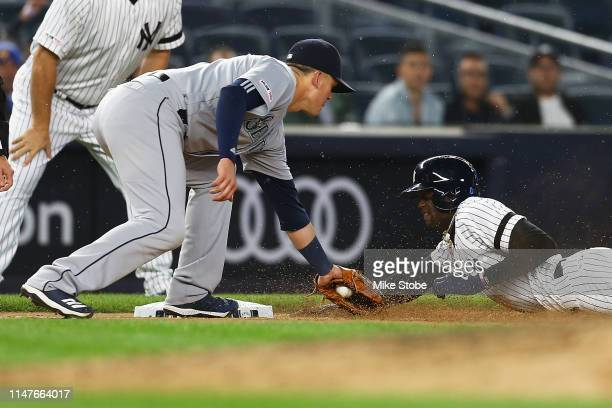 Cameron Maybin of the New York Yankees is tagged out at third base by Ryon Healy of the Seattle Mariners trying to advance on a throwing error at...