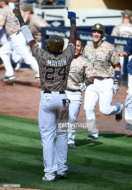 Cameron Maybin of the San Diego Padres celebrates after scoring the winning run during the ninth inning of a baseball game at Petco Park against the...