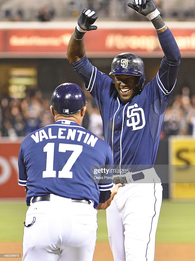 Cameron Maybin #24 of the San Diego Padres celebrates his walk-off single with Jose Valentin #17 during the eleventh inning of a baseball game against the Washington Nationals at Petco Park on June 7, 2014 in San Diego, California. The Padres won 4-3.