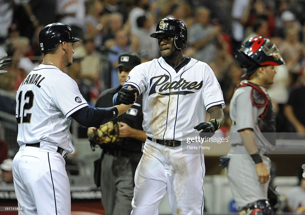Cameron Maybin #24 of the San Diego Padres, center, is congratulated by Yasmani Grandal #12, left, after hitting a two-run homer as Yadier Molina #4 of the St. Louis Cardinals looks on during the third inning of a baseball game at Petco Park on September 10, 2012 in San Diego, California.