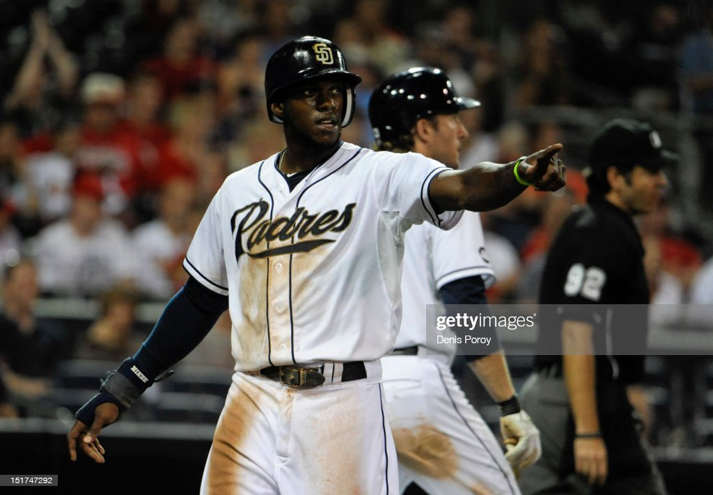 Cameron Maybin #24 of the San Diego Padres points back to first base after scoring during the seventh inning of a baseball game against the St. Louis Cardinals at Petco Park on September 10, 2012 in San Diego, California.