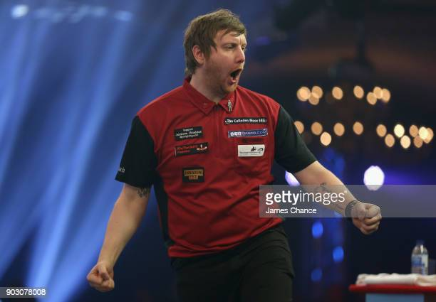 Cameron Menzies of Scotland celebrates while playing Conan Whitehead during the First Round of the BDO World Darts Championship at Lakeside Country...