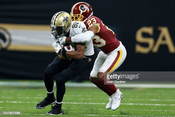 Cameron Meredith of the New Orleans Saints is tackled by Quinton Dunbar of the Washington Redskins during the first half at the MercedesBenz...