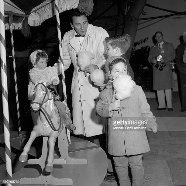 Cameron Mitchell and his kids play on the carousel ride and eat cotton candy at the premiere of the movie Carousel in Los AngelesCA