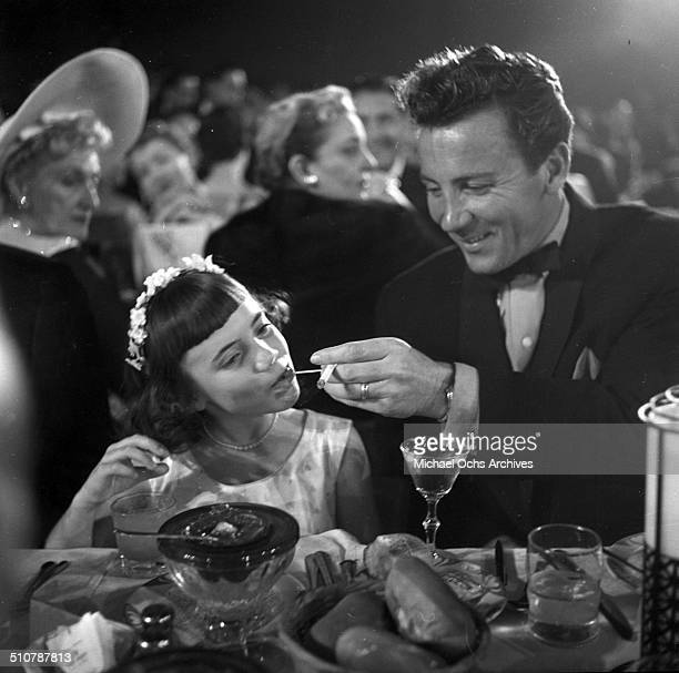 Cameron Mitchell feeds Melinda Marx Groucho Marx's daughter during the Emmy Awards in Los AngelesCA