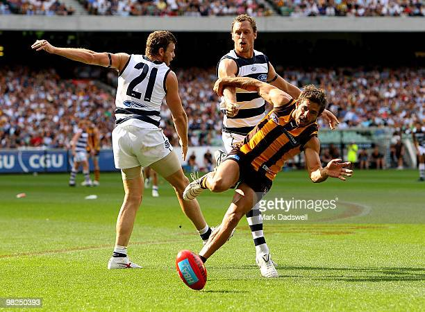 Cameron Mooney and James Kelly of the Cats spoil Chance Bateman of the Hawks during the round two AFL match between the Hawthorn Hawks and the...