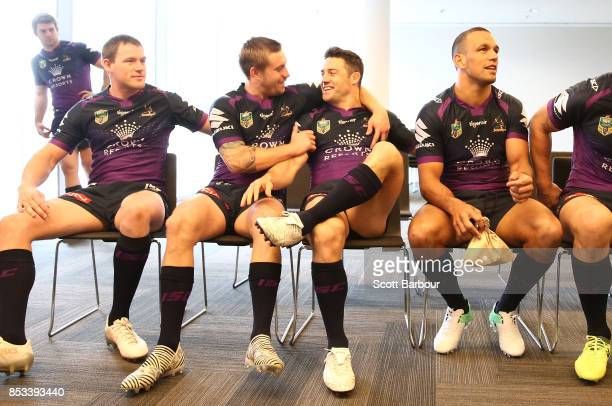 Cameron Munster and Cooper Cronk talk as they pose for their team photo with the ProvanSummons trophy during a Melbourne Storm NRL training session...