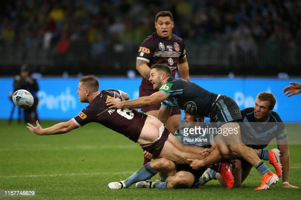 Cameron Munster of Queensland gets his pass away while being tackled during game two of the 2019 State of Origin series between the New South Wales...