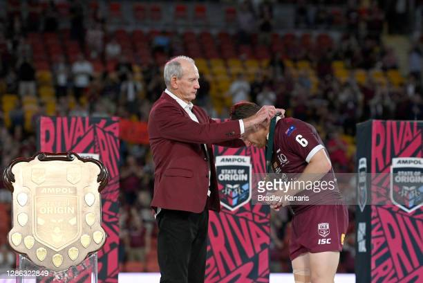 Cameron Munster of the Maroons is presented with the man of the match award by Maroons coach Wayne Bennett after game three of the State of Origin...