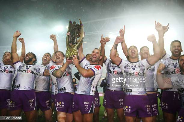 Cameron Munster of the Storm and Cameron Smith of the Storm celebrate with team mates after winning the 2020 NRL Grand Final match between the...