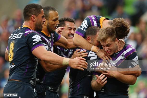 Cameron Munster of the Storm celebrates scoring a try with his teammates during the round four NRL match between the Melbourne Storm and the...