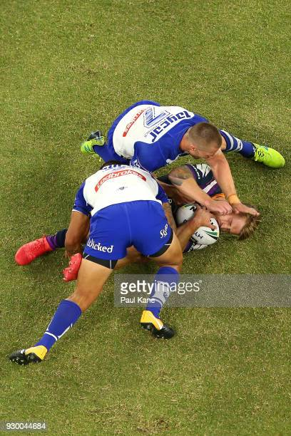 Cameron Munster of the Storm gets tackled by Kieran Foran and Michael Lichaa of the Bulldogs during the round one NRL match between the Canterbury...