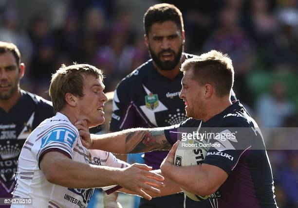 Cameron Munster of the Storm is challenged by Jake Trbojevic of the Sea Eagles during the round 21 NRL match between the Melbourne Storm and the...