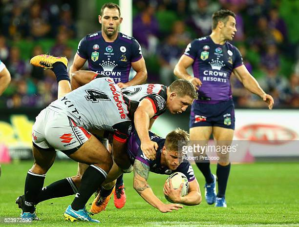 Cameron Munster of the Storm is tackled during the round eight NRL match between the Melbourne Storm and the New Zealand Warriors at AAMI Park on...
