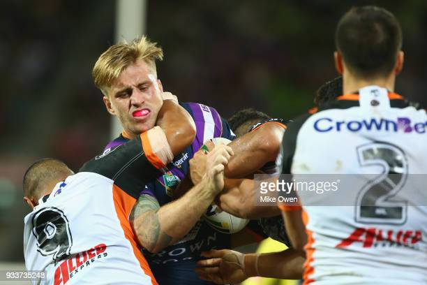 Cameron Munster of the Storm is tackled during the round two NRL match between the Melbourne Storm and the Wests Tigers at AAMI Park on March 17 2018...