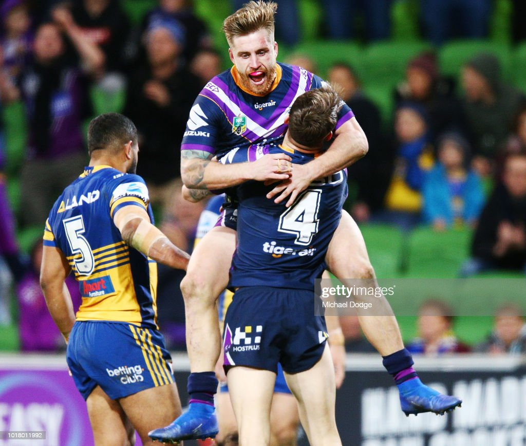 Cameron Munster of the Storm jumps on Curtis Scott of the Storm after he scores a try during the round 23 NRL match between the Melbourne Storm and the Parramatta Eels at AAMI Park on August 17, 2018 in Melbourne, Australia.