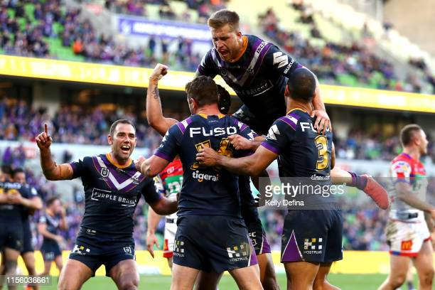 Cameron Munster of the Storm top and Cameron Smith of the Storm celebrate the try of Joe Stimson of the Storm during the round 14 NRL match between...