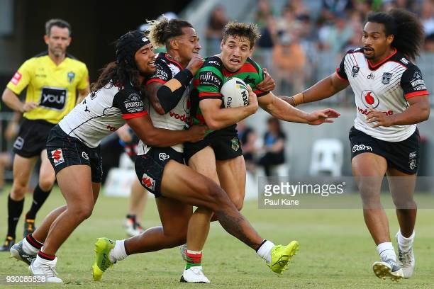 Cameron Murray of the Rabbitohs gets tackled by Isaiah Papali'i and James Gavet of the Warriors during the round one NRL match between the South...