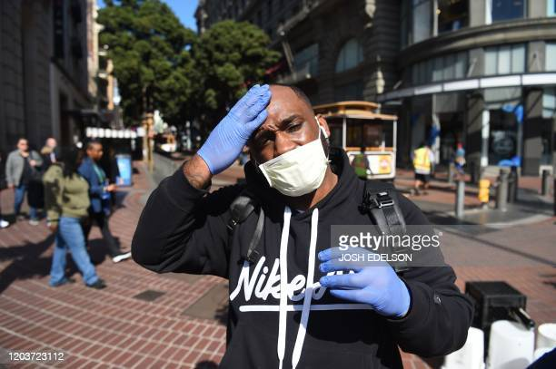 Cameron Nightingale adjusts his mask and gloves a precaution to protect himself from coronavirus while walking by cable car in San Francisco...