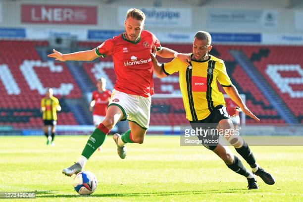 Cameron Norman of Walsall battles for possession with Aaron Martin of Harrogate Town during the Sky Bet League Two match between Harrogate Town and...