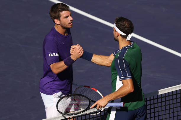 Cameron Norrie of Great Britain shakes hands with Grigor Dimitrov of Bulgaria hands after defeating him in their match on Day 13 of the BNP Paribas...