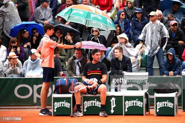 Cameron Norrie of Great Britain sits underneath an umbrella as play is stopped due to rain during his mens singles first round match against Elliot...