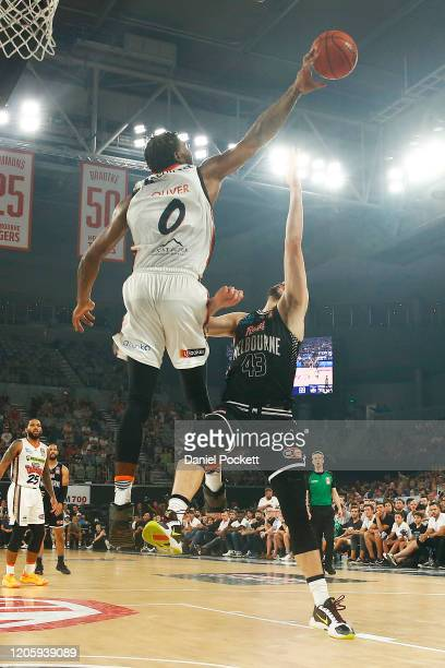 Cameron Oliver of the Taipans blocks Chris Goulding of United during the round 20 NBL match between Melbourne United and the Cairns Taipans at...