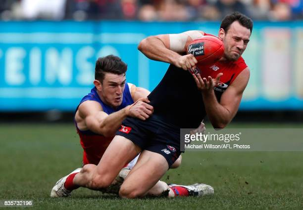 Cameron Pedersen of the Demons is tackled by Daniel McStay of the Lions during the 2017 AFL round 22 match between the Melbourne Demons and the...