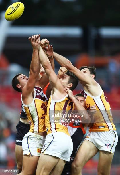 Cameron Rayner Stefan Martin and Oscar McInerney of the Lions compete for the ball during the round six AFL match between the Greater Western Sydney...