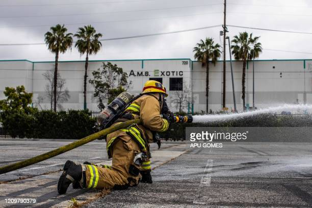 Cameron Richards a probationary firefighter holds a water hose in a morning training session of the LAFD Station No9 team at Skid Row on April 12...