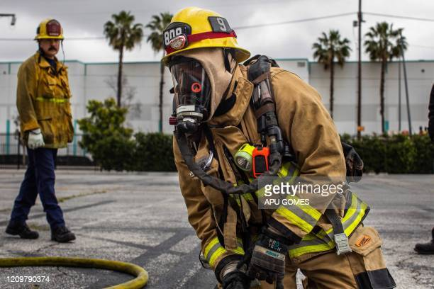 Cameron Richards a probationary firefighter wears a gas mask in a morning training session of the LAFD Station No9 team at Skid Row on April 12 2020...