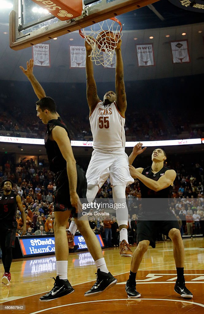 Cameron Ridley #55 of the Texas Longhorns slam dunks over Stefan Nastic #4 and Reid Travis #22 of the Stanford Cardinal at the Frank Erwin Center on December 23, 2014 in Austin, Texas.
