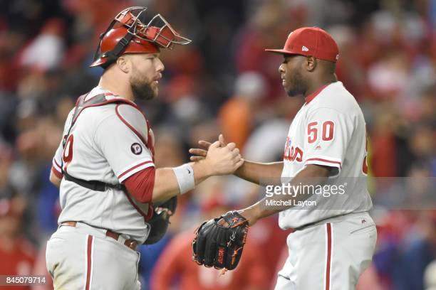Cameron Rupp of the Philadelphia Phillies and Hector Neris celebrate a win after a baseball game at Nationals Park on September 9 2017 in Washington...