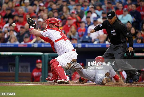 Cameron Rupp of the Philadelphia Phillies catches a throw as Zack Cozart of the Cincinnati Reds slides safely into home plate in the first inning...