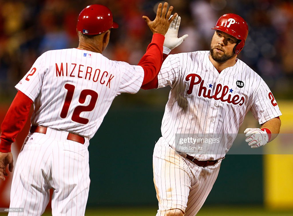 Cameron Rupp #29 of the Philadelphia Phillies is congratulated by third base coach John Mizerock #12 after hitting a three run home run during the eighth inning of a MLB game at Citizens Bank Park on August 28, 2015 in Philadelphia, Pennsylvania. The Phillies defeated the Padres 7-1.