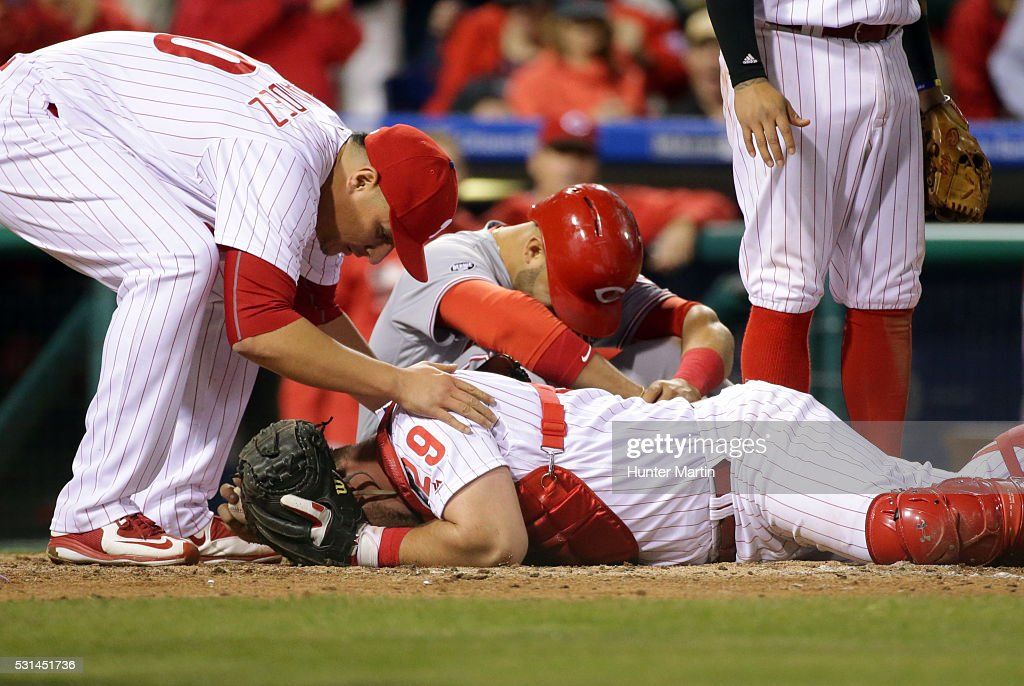 Cameron Rupp #29 of the Philadelphia Phillies lays on the ground after tagging out Eugenio Suarez #7 of the Cincinnati Reds during a collision at home plate in the ninth inning during a game at Citizens Bank Park on May 14, 2016 in Philadelphia, Pennsylvania. The Phillies won 4-3.