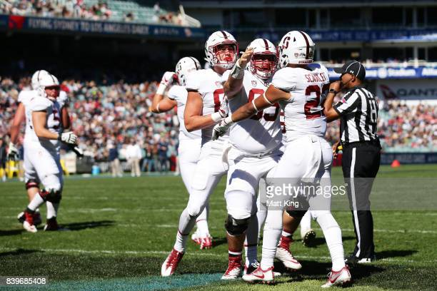 Cameron Scarlett of Stanford celebrates with team mates after scoring a touchdown during the College Football Sydney Cup match between Stanford...