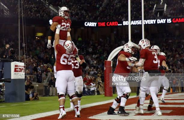 Cameron Scarlett of the Stanford Cardinal is lifted in the air by Brian Chaffin of the Stanford Cardinal after Scarlett ran in for a touchdown...