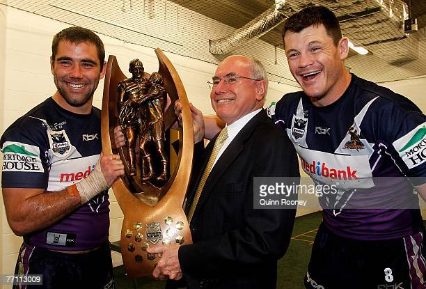Cameron Smith and Ben Cross of the Storm pose for a photo with Prime minister John Howard after winning the NRL Grand Final match between the...