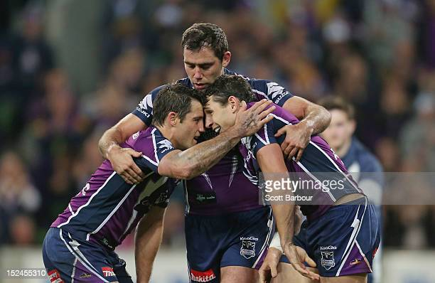 Cameron Smith and Cooper Cronk congratulate Billy Slater of the Storm after he scored a try in the second half during the NRL Preliminary Final match...