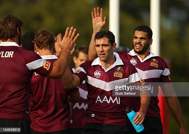 Cameron Smith and Greg Inglis of the Maroons high five their team mates during a Queensland Maroons State of Origin training session at Xavier...