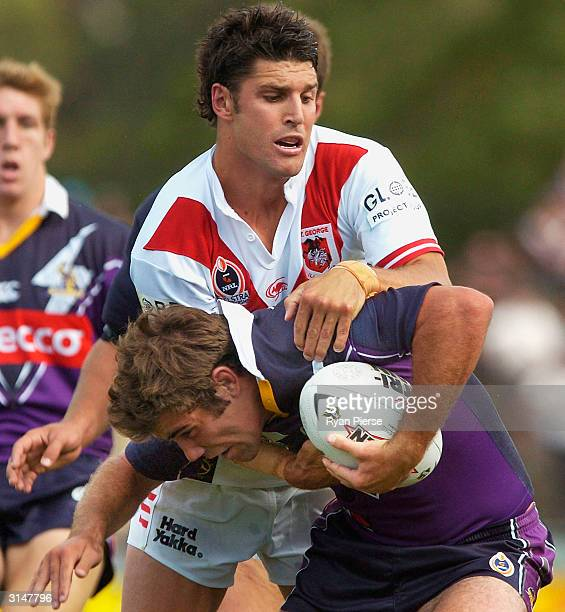 Cameron Smith for the Storm is tackled by Trent Barrett for the Dragons during the round 3 NRL match between the Melbourne Storm and the StGeorge...