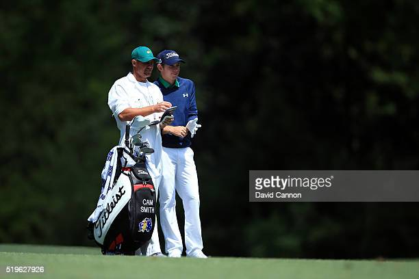 Cameron Smith of Australia and caddie Adrian Schwartzel prepares to pla his second shot on the fifth hole during the first round of the 2016 Masters...
