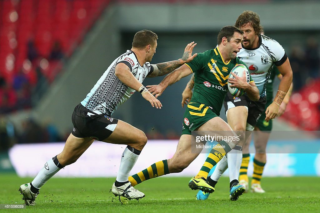Cameron Smith (C) of Australia cuts between Tariq Sims (L) and Ashton Sims (R) of Fiji during the Rugby League World Cup Semi Final match between Australia and Fiji at Wembley Stadium on November 23, 2013 in London, England.