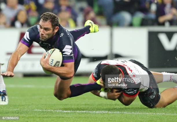 Cameron Smith of the Melbourne Storm is tackled during the round eight NRL match between the Melbourne Storm and the New Zealand Warriors at AAMI...